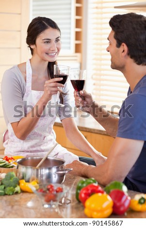 Portrait of a couple having a glass of wine while cooking in their kitchen - stock photo