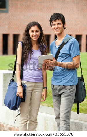 Portrait of a couple holding a tablet computer outside a building - stock photo