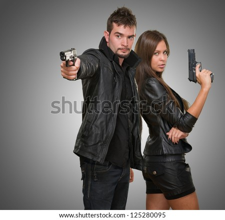 Portrait of a couple holding guns against a grey background