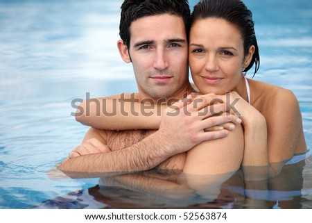 Portrait of a couple in a swimming pool - stock photo