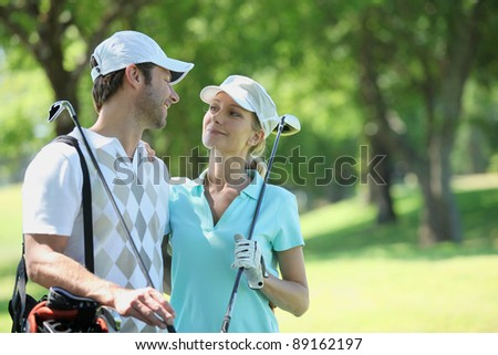 portrait of a couple in golf clothes - stock photo