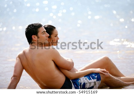 Portrait of a couple lying on the sand at the seaside