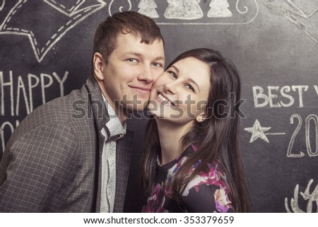Portrait of a couple men and women on the background walls are covered with Christmas words - stock photo