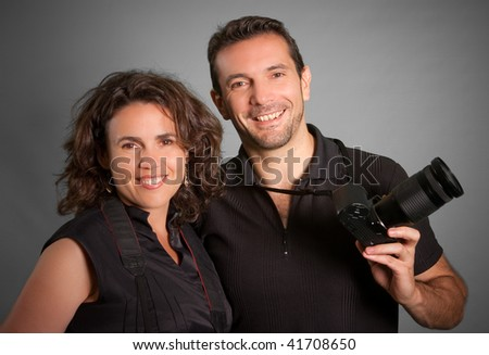 Portrait of a couple of cheerful photographers