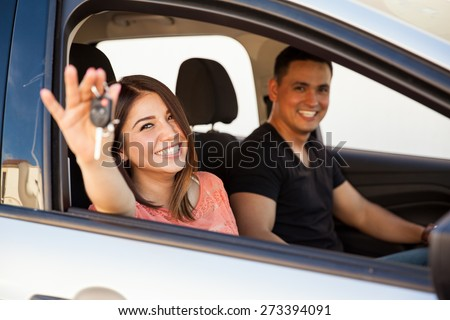 Portrait of a couple of happy  newlyweds enjoying their brand new car - stock photo
