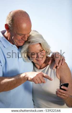 Portrait of a couple of smiling seniors with a phone - stock photo