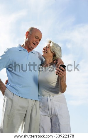 Portrait of a couple of smiling seniors with a phone
