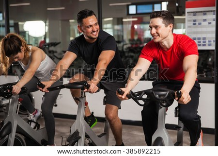 Portrait of a couple of young men talking and laughing while doing some spinning at a gym - stock photo