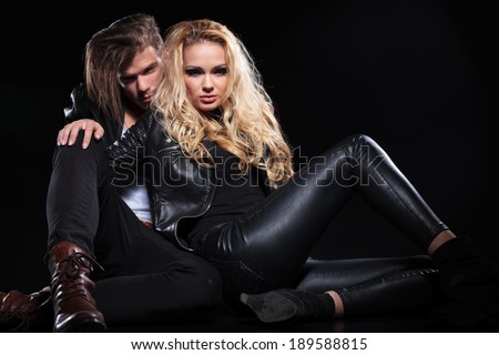 portrait of a couple relaxing on the floor while looking into the camera. on black background