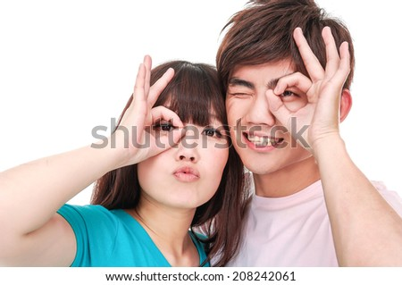 Portrait of a couple showing an OK sign on eye - stock photo
