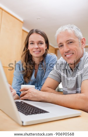 Portrait of a couple using a laptop while having tea in their kitchen