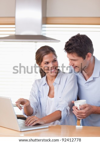 Portrait of a couple using a laptop while having tea in their kitchen - stock photo