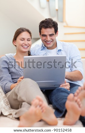 Portrait of a couple using a laptop while lying on a sofa in their living room - stock photo
