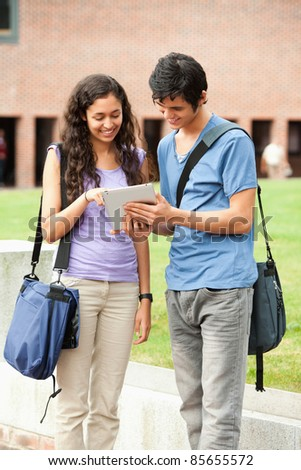 Portrait of a couple using a tablet computer outside a building - stock photo