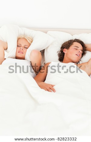 Portrait of a couple waking up in their bedroom - stock photo
