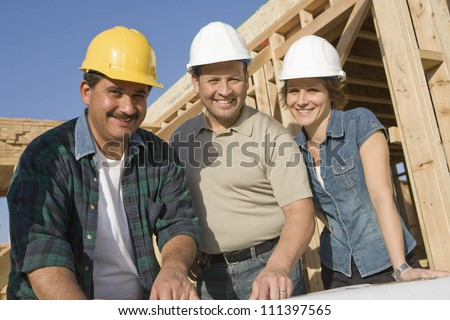 Portrait of a couple with architect and blueprint at construction site - stock photo