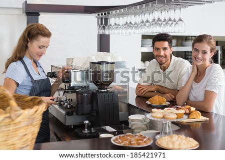 Portrait of a couple with female cafe owner at the coffee shop - stock photo