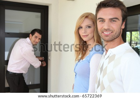 Portrait of a couple with realtor - stock photo