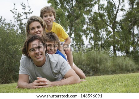 Portrait of a couple with two sons lying on top of each other in park - stock photo
