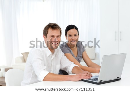 Portrait of a couple working on their laptop in the living room at home - stock photo
