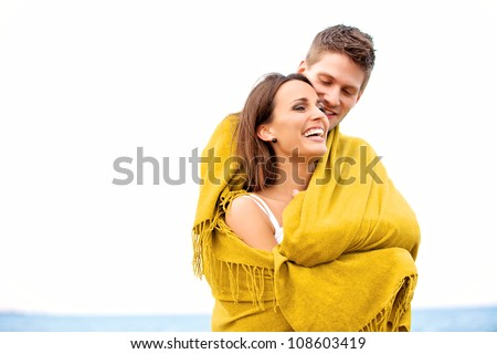Portrait of a couple wrapped in a blanket while on a sea looking happy - stock photo