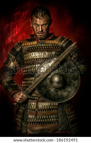 Portrait of a courageous ancient warrior in armor with sword and shield.