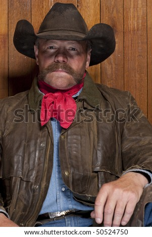 Portrait of a cowboy with a mustache in front of a rough wood wall. He is staring at the camera with a serious expression. Vertical format. - stock photo
