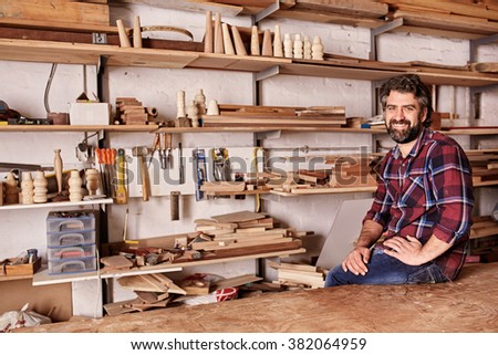 Portrait of a craftsman smiling at the camera while sitting on the edge of workbench, in his woodwork studio, with long shelves behind him holding planks of wood and wooden items. - stock photo