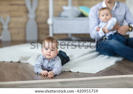 Portrait of a crawling baby on the carpet in his room - stock photo