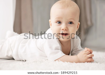 Portrait of a crawling baby on the carpet in my room - stock photo