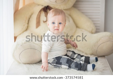 Portrait of a crawling baby on the window in his room - stock photo