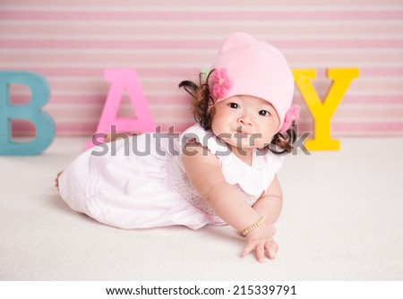 Portrait of a crawling pretty baby with pink hat on the bed in her room. text concept - stock photo