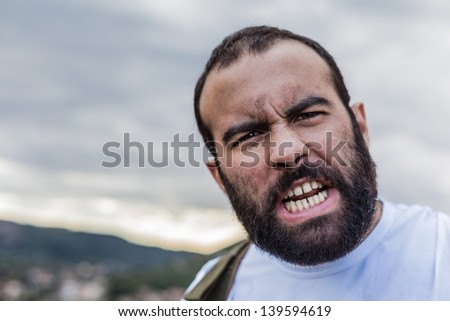 portrait of a crazy man showing the teeth in anger - stock photo