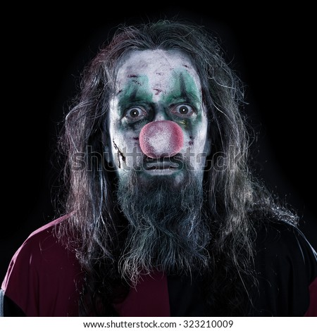 Portrait of a creepy and bloody clown in front of black background, concept Horror or Halloween - stock photo