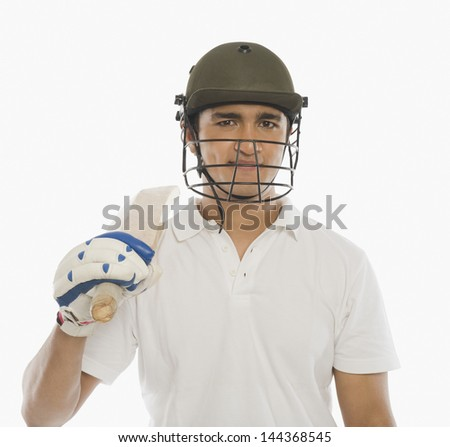 Portrait of a cricket batsman holding a bat and smiling - stock photo