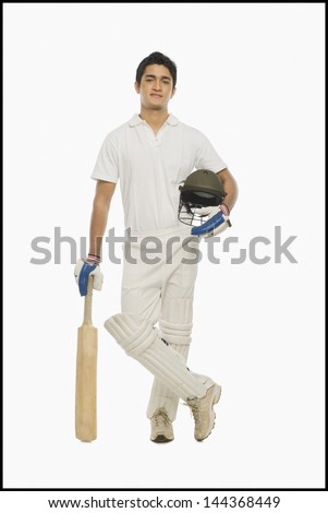 Portrait of a cricket batsman standing with a bat and a helmet - stock photo