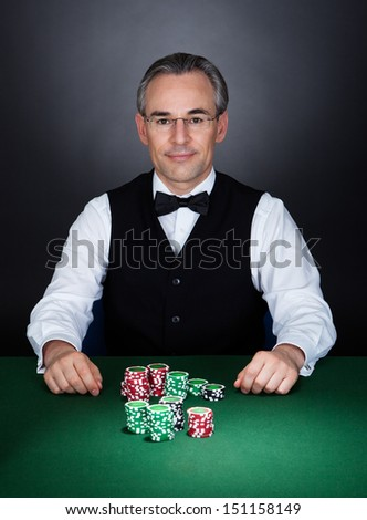 Portrait of a croupier with gambling chips on table - stock photo