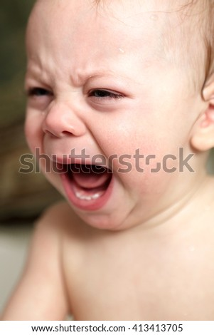 Portrait of a crying baby in bathroom - stock photo