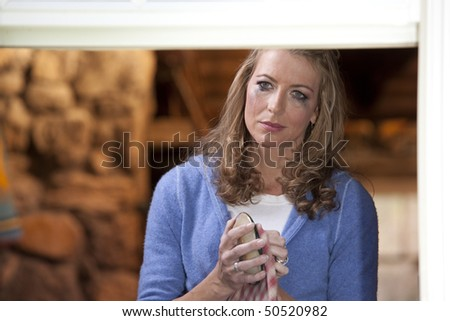 Portrait of a crying woman drying a dish and staring into the distance as mascara runs down her face. Horizontal format. - stock photo