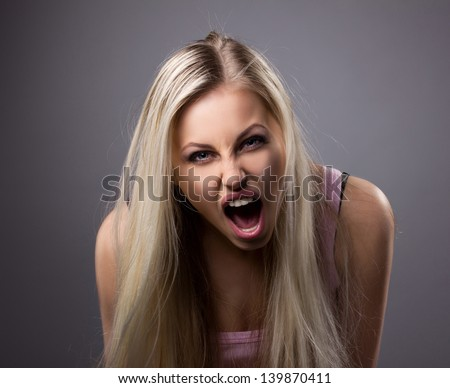 portrait of a crying young  woman with blond long hair on grey dark background - stock photo