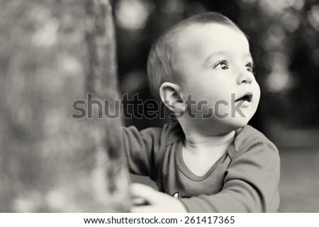 portrait of a curios little boy in the nature - black and white - stock photo