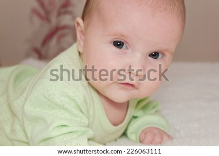 portrait of a curious baby lying on the bed. - stock photo