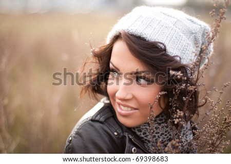 Portrait of a curly brunette in the field - stock photo