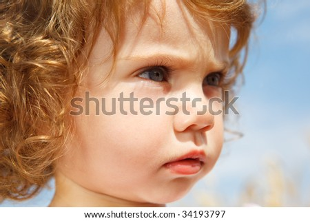 Portrait of a curly concentrated little  girl - stock photo