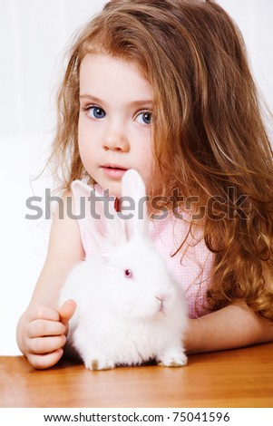 Portrait of a curly girl and white rabbit - stock photo