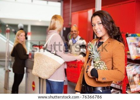 Portrait of a customer carrying pineapple in supermarket with people in the background - stock photo