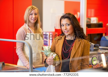 Portrait of a customer holding pineapple with shop assistant in the background