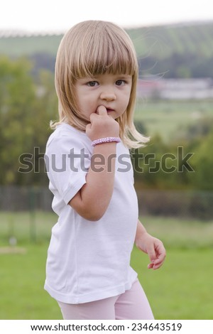 Portrait of a cut child girl with a finger in her mouth biting her nail standing in park or garden in summer. - stock photo