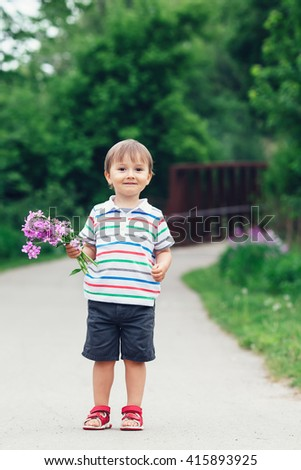 Portrait of a cute adorable funny little smiling boy toddler walking in park with lilac purple pink flowers in hands on bright summer day, mothers day holiday concept  - stock photo