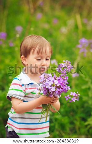 Portrait of a cute adorable little boy toddler standing in the forest field meadow with lilac purple flowers in his hands and blowing them on a bright summer day, funny card with copy space for text - stock photo